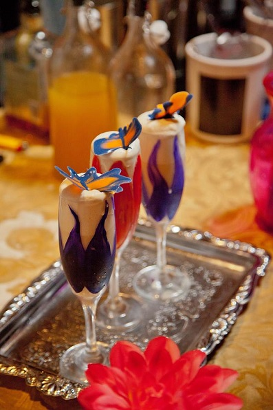 Three Champagne Glasses on a Silver Tray Filled With a White Foamy Cocktail With a Purple or Red Colour Shaped Like a Flower Around it and Topped With a Butterfly