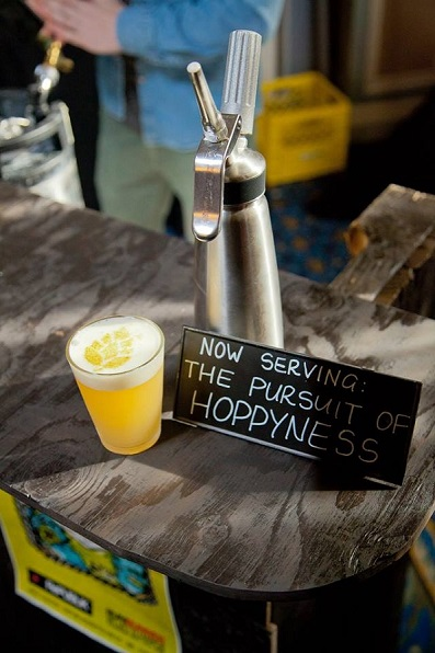 A Glass Sitting on a Grey Bar With a Bright Yellow Cocktail and One Inch of a White Foam on the Top With A Hop Drawn in the Foam