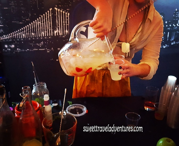 A Woman Pouring a Lemonade Cocktail With Strawberries into a Plastic Cup From a Glass Pitcher Over a Dark Table With Mixology Things, in the Background is Pictures of Cityscapes and a Bridge Lit Up at Night