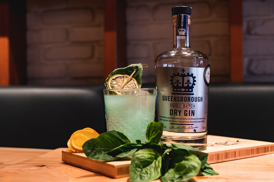 A Short Glass With an Aqua Coloured Liquid and Ice, Garnished With a Lemon Wedge and Basil, With a Bottle of Queensborough Gin on the Right, Both Sitting on Top of a Wooden Cutting Board and Wooden Table, With Basil in Front of the Drink Sitting on the Cutting Board and Lemon Rind on the Left, With a Black Leather Looking Bench Style Seating Behind