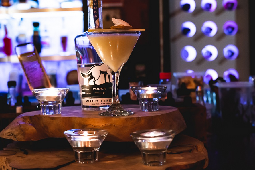A Martini Glass With a Yellow Liquid Topped With White Cream With a Bottle of Vodka Behind, Sitting on a Piece of Wood With Glass Votives All Around and a Bar Behind